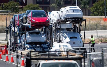 "Tesla Motors Inc.'s vehicles are loaded onto a car hauler at the company's production plant in Fremont, California, U.S., on Wednesday, June 20, 2018. Elon Musk, Tesla's chief executive officer, said the company needed another general assembly line to reach its production targets for the Model 3. ""A new building was impossible, so we built a giant tent in 2 weeks,"" Musk said on Twitter. Photographer: David Paul Morris/Bloomberg"