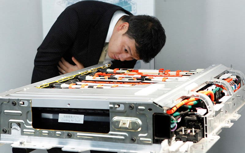 A man examines a lithium-ion battery for Toyota Motor Corp.'s Prius plug-in hybrid vehicle during the unveiling in Tokyo, Japan, on Tuesday, Nov. 29, 2011.  Photographer: Kiyoshi Ota/Bloomberg
