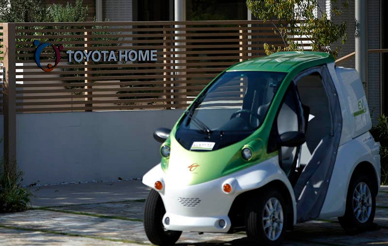 A Toyota Auto Body Co. Coms super-compact electric vehicle (EV) is parked outside a model smart house, developed by Toyota Motor Corp.'s Toyota Housing Corp. unit, inside the