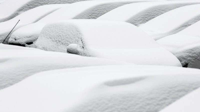 Snow-covered cars are parked in Freiburg, southern Germany, Sunday, March 18, 2018.  (Patrick Seeger/dpa via AP)